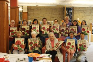 Image of a group of library patrons with their finished floral paintings.