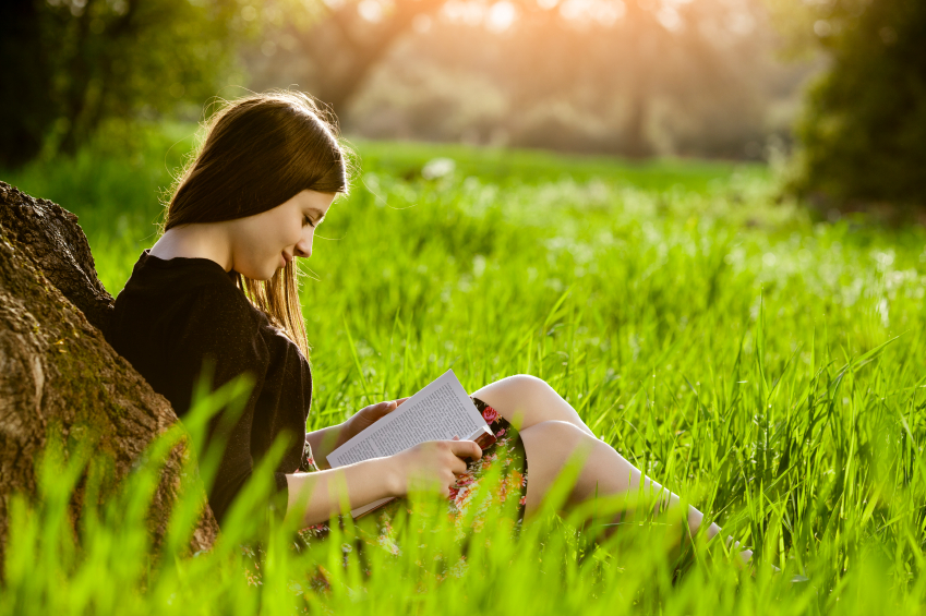 Teenage girl reading book in meadow